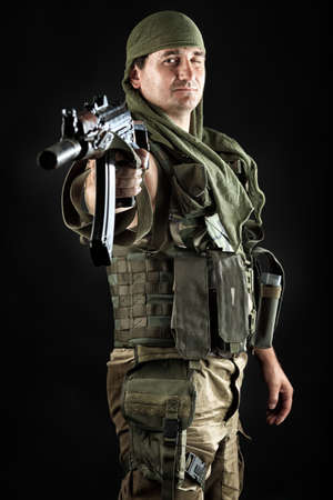 commando: Shot of a conceptual soldier painted in khaki colors. Over black background.