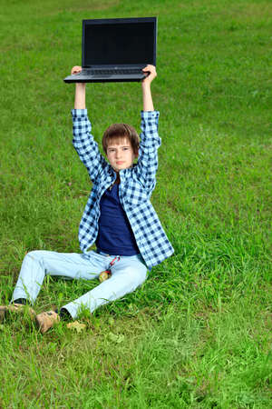 Portrait of a boy teenager with his laptop on a grass at a park. photo