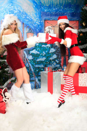 Two sexy girls are selected from each other gift over  Christmas background. photo