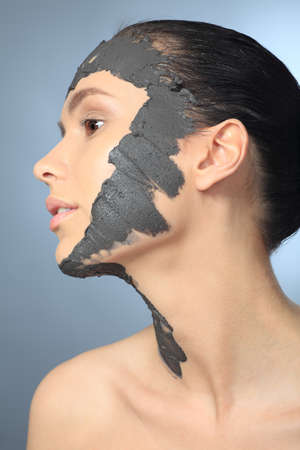Portrait of a woman with spa mud mask on her face. photo