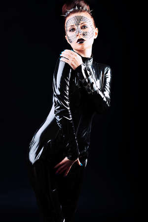 latex woman: Conceptual shot of a woman in black glossy overall and metal buttons on her face.