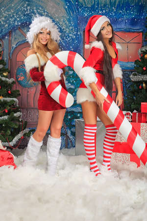 Two sexy young women in Christmas clothes posing over Christmas background. photo