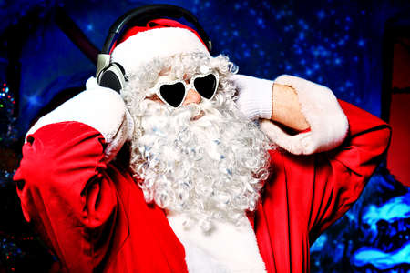 Santa Claus is listening to music in headphones. Christmas. Stock Photo - 11639316