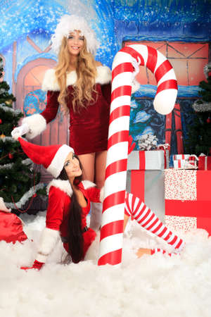 Beautiful young woman in Santa Claus clothes over Christmas background. Stock Photo - 11639332