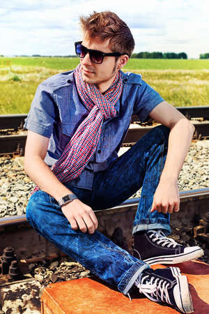 young male model: Portrait of a handsome young man posing at a railroad. Stock Photo