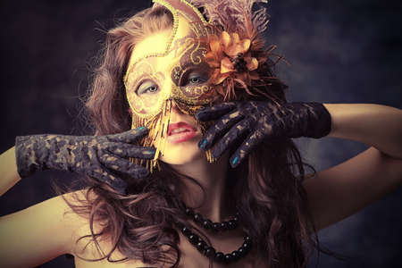 Portrait of an attractive  woman in mask posing at studio. photo