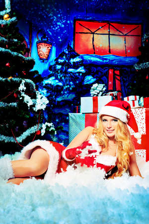 sexy fur: Beautiful young woman in Santa Claus clothes over Christmas background.