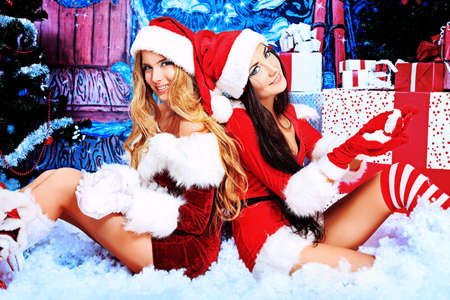 sexy santa girl: Two beautiful young women in Christmas clothes posing over Christmas background.