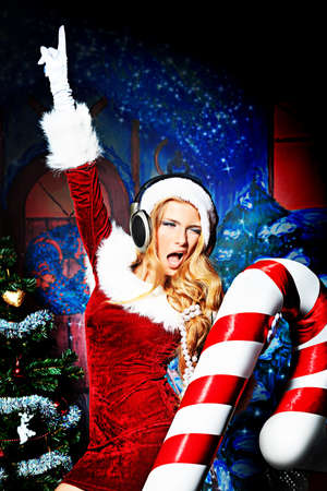 sexy woman disco: Beautiful young woman in Santa Claus clothes and headphones over Christmas background. Stock Photo