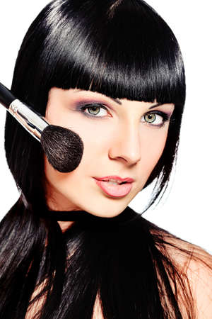 Beautiful young woman posing with makeup brush. Isolated over white. photo