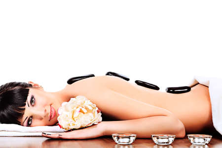 hot rock therapy: Beautiful woman relaxing in a spa salon. Isolated over white.