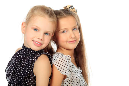 Portrait of two little girls sisters posing at studio. Isolated over white. Stock Photo - 11692024