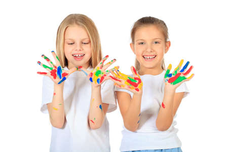Portrait of two cute girls enjoying painting. Education. Isolated over white background. photo