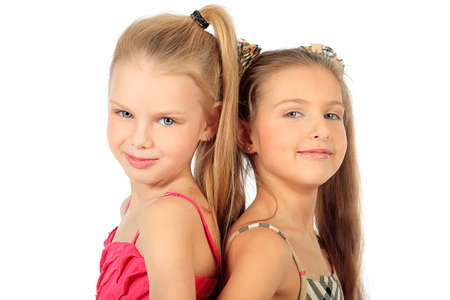 Portrait of two little girls sisters posing at studio. Isolated over white. Stock Photo - 11691060