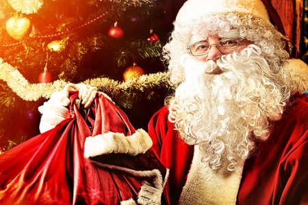 nick: Santa Claus sitting with presents over Christmas background.