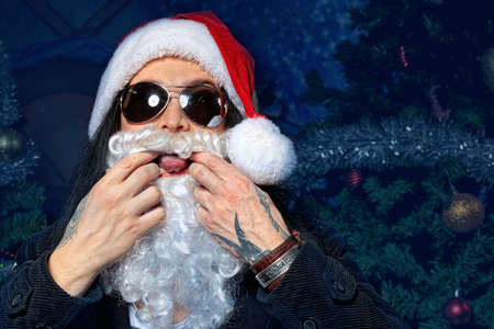Portrait of a funny young man in Santa Claus costume making faces. Christmas. photo