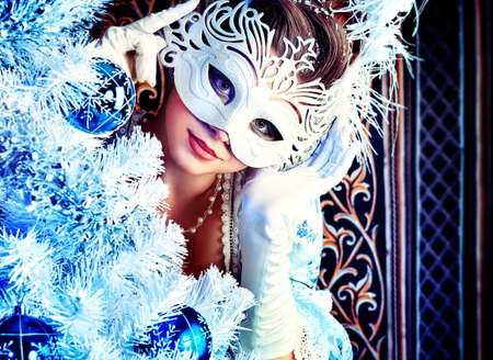 masquerade masks: Portrait of the elegant woman posing with Christmas tree over vintage background.