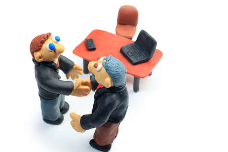 Shot of two plasticine businessmen shaking their hands in office. Isolated over white background. photo
