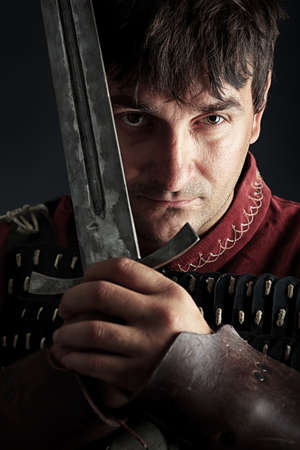Portrait of a medieval male knight in armor over black background.