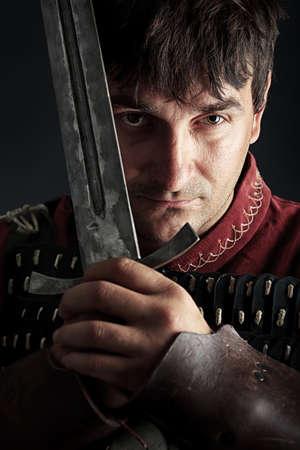 caballero medieval: Retrato de un caballero medieval con armadura masculina sobre fondo negro.