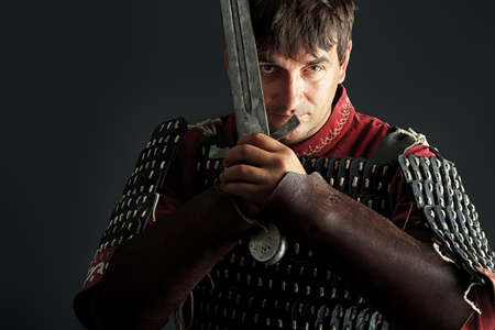 swords: Portrait of a medieval male knight in armor over black background.