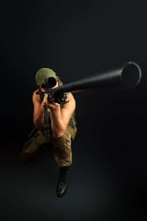 sniper rifle: Shot of a conceptual soldier painted in khaki colors. Over black background.