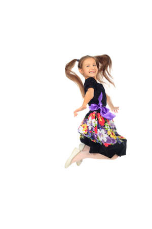 Portrait of happy 7 years old girl jumping at studio. Isolated over white background. Stock Photo - 11885357