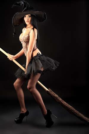 strega: Incantevole strega di Halloween con scopa su sfondo nero. Archivio Fotografico