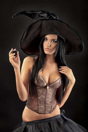 halloween costume: Charming halloween witch over black background. Stock Photo