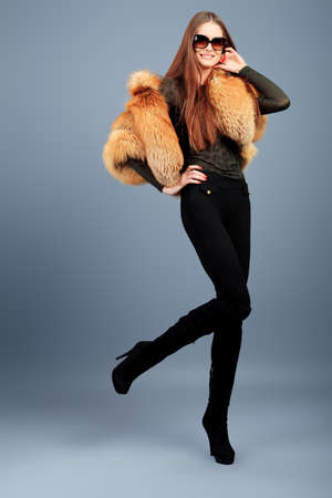 Portrait of a beautiful young woman in a fur over grey background. photo