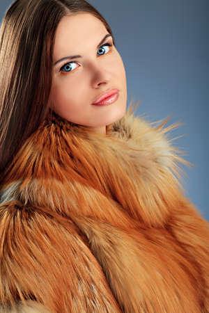Portret van een mooie jonge vrouw in een bont over grijze achtergrond.