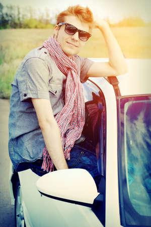 Knappe jonge man die 's zomers tochtje op een auto.