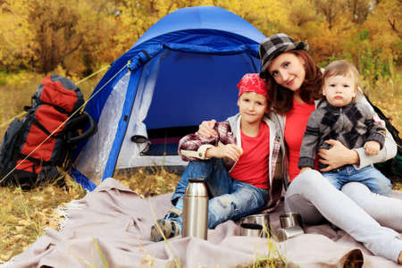 Happy family having a rest outdoor in tent. photo