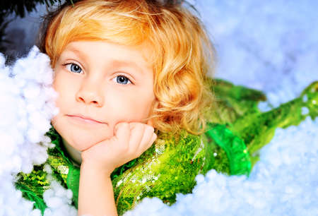 Happy little girl in Christmas dress lying in snow. Stock Photo - 11977398