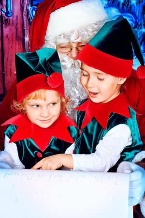Santa Claus sitting with two little cute elves over Christmas background.  Stock Photo - 11972293