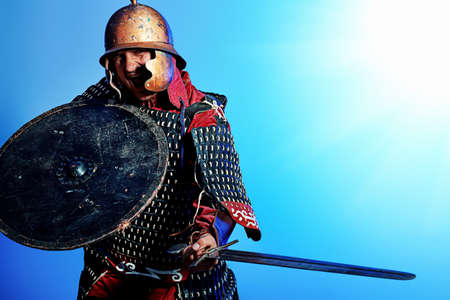 Portrait of a medieval male knight in armor over blue background. photo