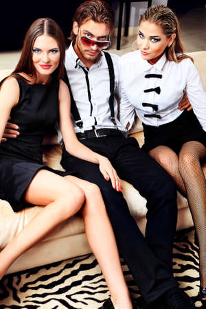 Portrait of a handsome fashionable man with two charming women posing in the interior. photo
