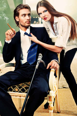 man smoking: Portrait of a handsome fashionable man with  charming woman posing in the interior. Stock Photo
