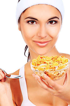 Portrait of a beautiful young woman eating cereal  Isolated over white background Stock Photo - 13451050