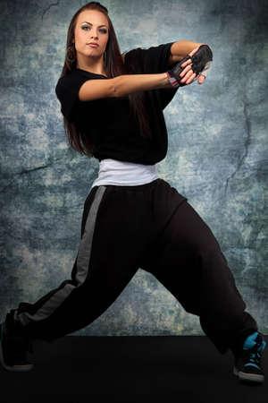 Modern teenage girl dancing hip-hop at studio. photo