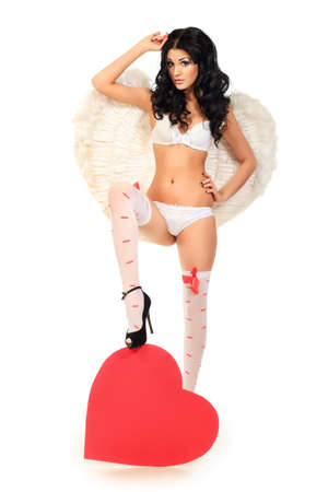 Sexual young woman angel posing with red heart. Isolated over white background. photo