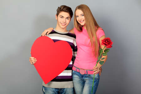 Happy young love couple posing together with red heart and rose.  photo