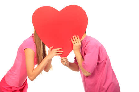 secret love: Happy young love couple kissing behind red heart. Isolated over white background.