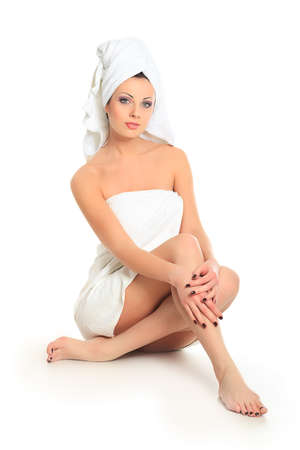 woman in towel: Beautiful young woman sitting in white towel. Spa, healthcare. Isolated over white. Stock Photo