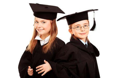Portrait of two children in a graduation gown. Education. Isolated over white. photo