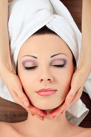 face massage: Beautiful young woman on a massage at a salon. Beauty, healthcare. Stock Photo