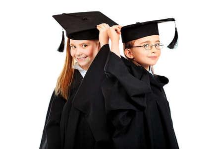 toga graduacion: Retrato de dos niños en un vestido de graduación. Educación. Aislado en blanco.