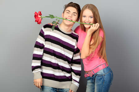 Happy young love couple posing together with red rose.  photo