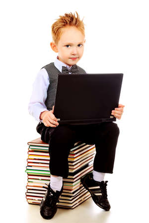 Shot of an emotional boy learning with his books and laptop. Isolated over white background. photo