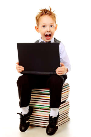 Shot of an emotional boy learning with his books and laptop. Isolated over white background. Stock Photo - 12073328